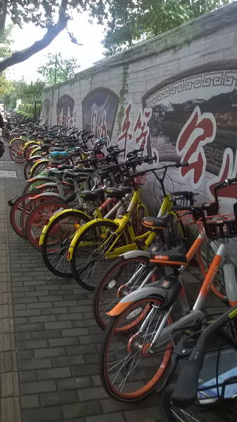 a row of shared bikes outside a subway station in Nanjing